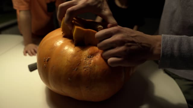 happy halloween. father and sons carving pumpkin on the table in the home. family preparing for holiday. top view. close up - zucca legenaria video stock e b–roll