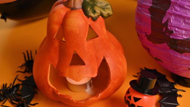 Happy Halloween! Pumpkin candlestick in hands. Various festive decor on an orange background. High quality 4k footage