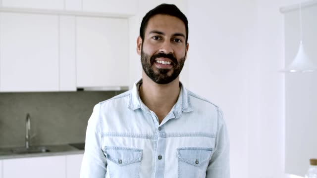 Happy handsome dark haired Latin man posing in kitchen