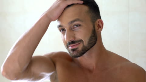 glücklich, gut aussehender mann überprüfung haar vor spiegel im badezimmer, morgen - gutaussehend stock-videos und b-roll-filmmaterial