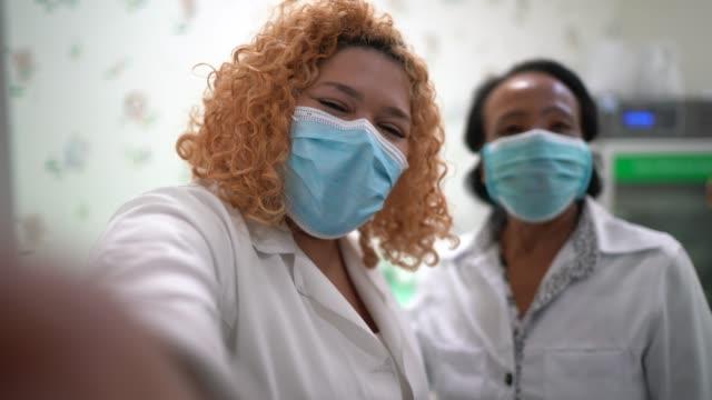 vídeos de stock e filmes b-roll de happy healthcare coworkers taking a selfie at hospital - fotografar