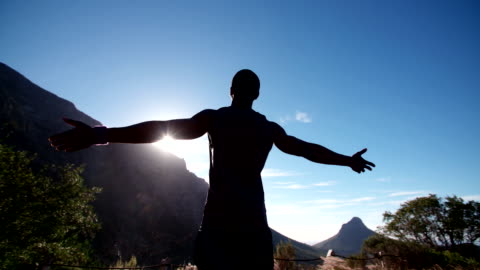 Happy healthy athlete appeciating the sun while on a run Rear view of a male athlete with his arms outstretched, looking out over a mountain with the sun shining on him, slow motion freedom stock videos & royalty-free footage