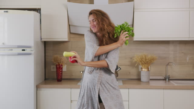 Happy Healthy Pregnancy Concept. Pregnant Woman Dancing And Cooking On Kitchen.