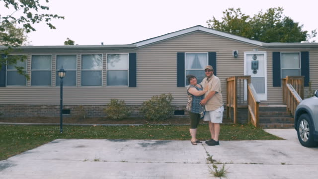 happy heavy couple hugging in front of a manufactured home - caravan stock videos & royalty-free footage