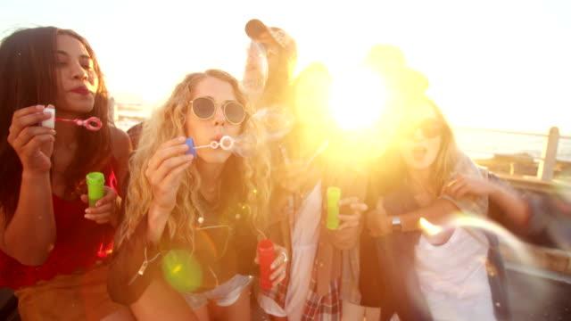 Amici hipster felice festeggiando con le bollicine Esterno al tramonto - video