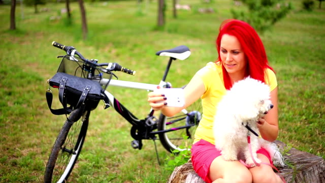 happy hipster girl with her dog and bike - bichon frisé video stock e b–roll