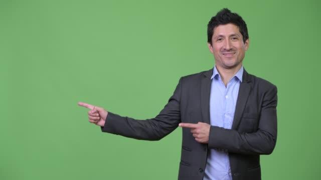 glad spansktalande affärsman visar något - kostym sida bildbanksvideor och videomaterial från bakom kulisserna