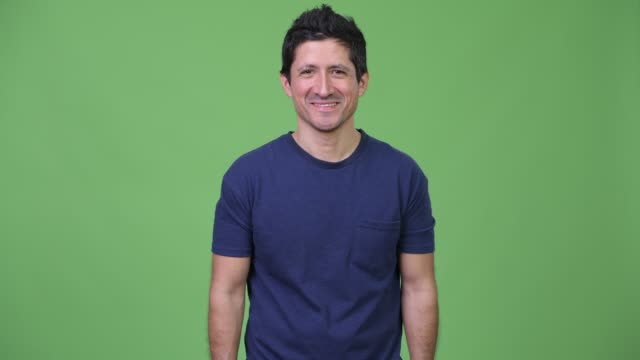 happy hispanic man smiling against green background - spanish and portuguese ethnicity stock videos & royalty-free footage