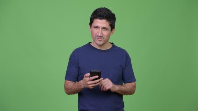 전화를 사용 하는 동안 생각 하는 행복 한 히스패닉 남자 - 한 명의 중년 남자만 스톡 비디오 및 b-롤 화면