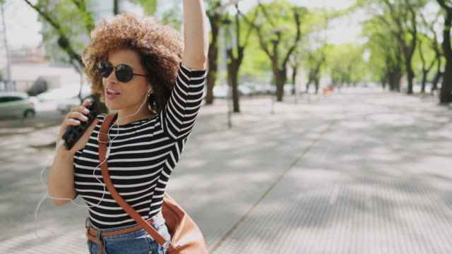 Happy Hispanic woman listening to music and dancing on the street video