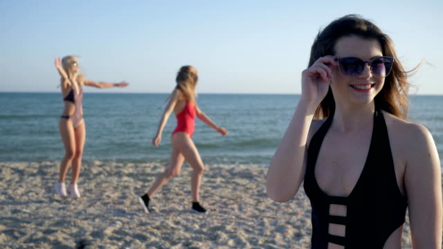 happy holidays, portrait of laughing girl in sunglasses and swimsuit on background of cheerful girlfriends at beach - happy holidays stock videos & royalty-free footage