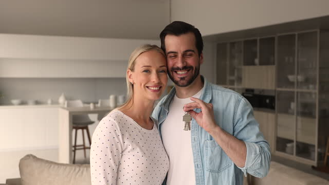 Happy homeowners couple looking at camera show bunch of keys