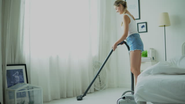 Happy housewife cleaning the room with vacuum cleaner