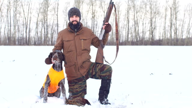 Happy hunter with dog and their game. Good day for hunting