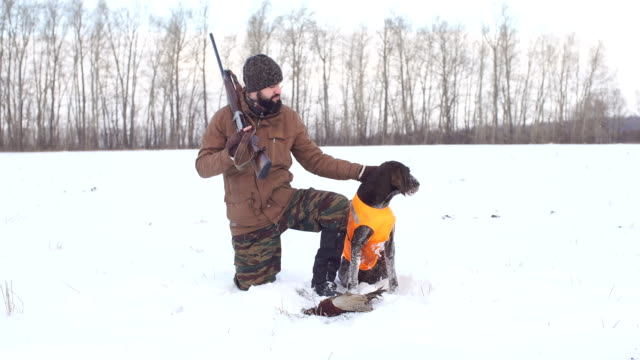 happy hunter with dog and their game