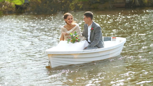 Happy husband and wife are sitting in a boat and laughing at their joyful life.