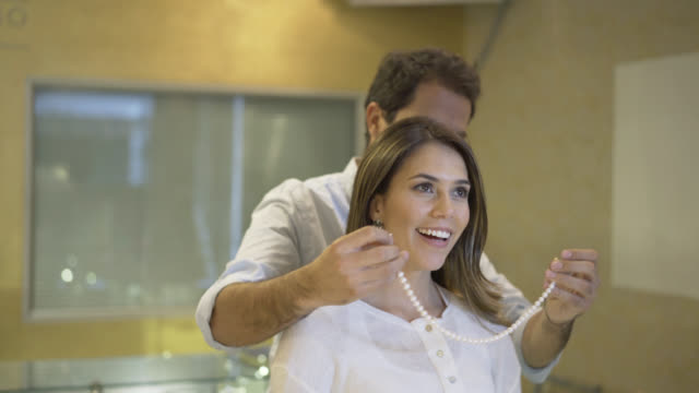 Happy husband trying on a pearl necklace on his wife