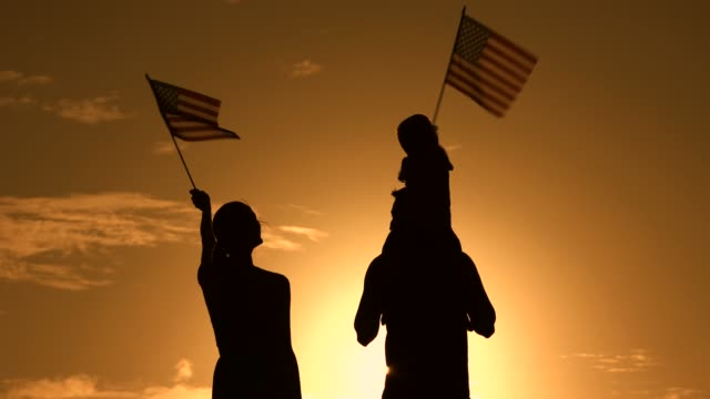 Happy Independence day Happy family waving with American flags at sunset. Election, Independence day concept. family 4th of july stock videos & royalty-free footage