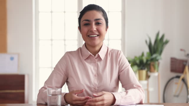 Happy indian business woman making video conference call in office
