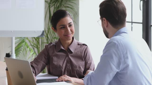 vidéos et rushes de femme d'affaires indienne indienne heureuse et poignée de main caucasienne d'homme d'affaires dans le bureau - relation client