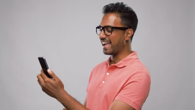 happy indian man in glasses using smartphone