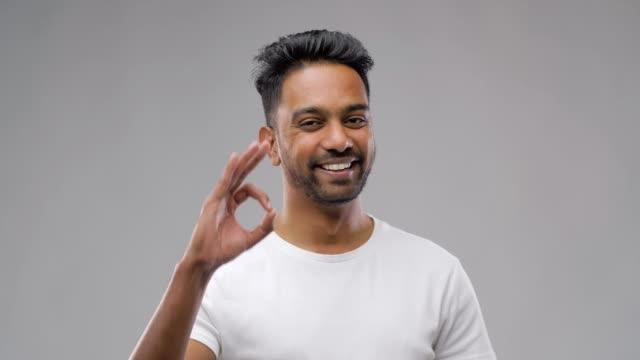 vídeos de stock e filmes b-roll de happy indian man in t-shirt showing ok hand sign - teeshirt template