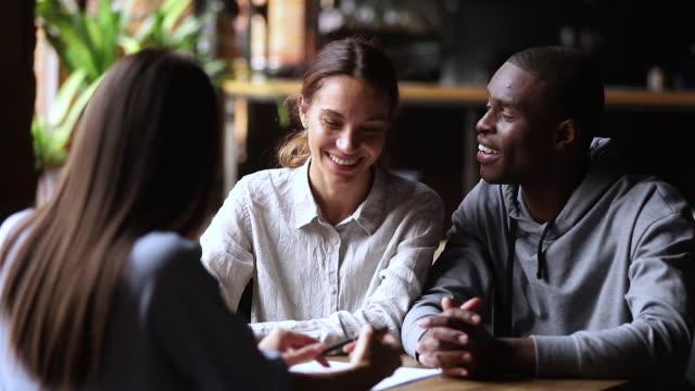 vídeos y material grabado en eventos de stock de feliz pareja interracial clientes firman contrato de inversión de préstamo agente de apretón de manos - acuerdo