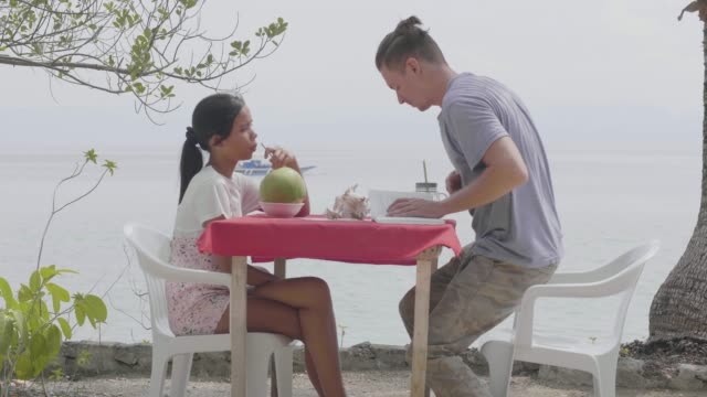 Happy interracial couple having date at the seaside cafe drinking fresh juice.