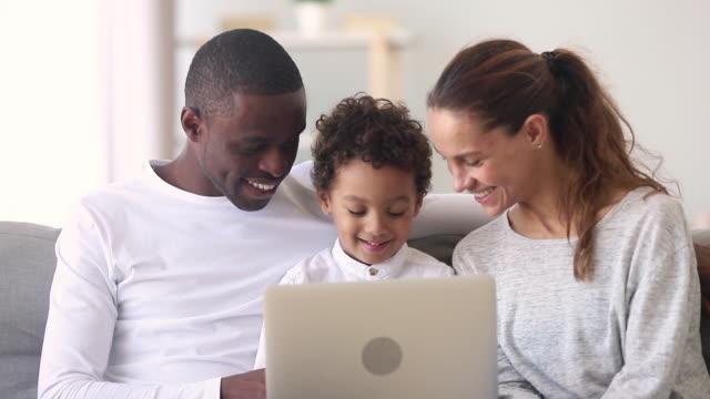 lycklig interracial familj mamma pappa och lille son använda laptop - parent talking to child bildbanksvideor och videomaterial från bakom kulisserna