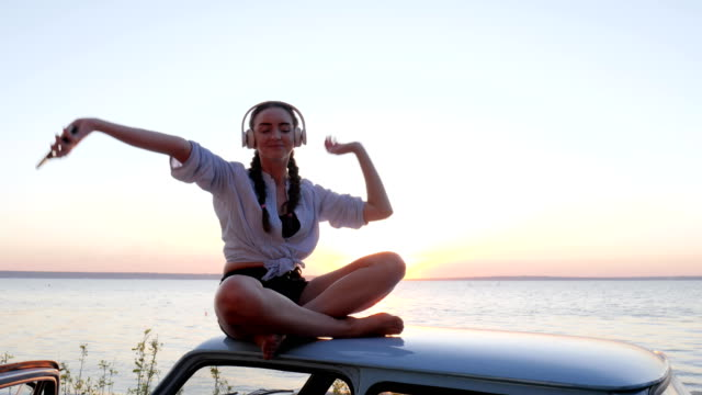 Happy Journey, pleasure of summer rest on seafront, girl Enjoying music at roof of automobile on shore river video