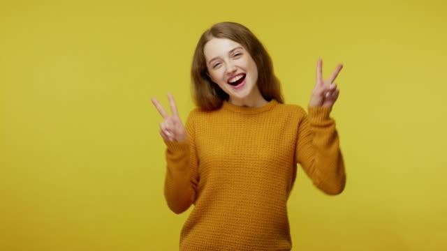 vídeos de stock, filmes e b-roll de feliz alegre menina bonita em roupa casual mostrando gesto de vitória com os dedos, fazendo duplo v sinal - amarelo