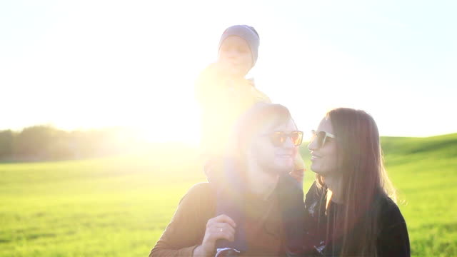 happy joyful smiling young parents family father mother and little son on shoulders having fun outdoors in nature on green meadow grass background - slow motion - key ring stock videos & royalty-free footage