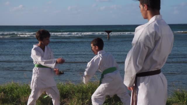 若い男の子の戦いとトレーニングを見て幸せな空手スポーツ インストラクター ビデオ
