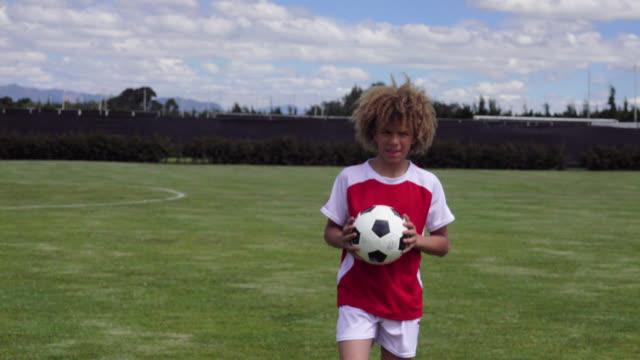 vídeos de stock e filmes b-roll de happy kid at a soccer field holding a ball while facing camera smiling - equipamento desportivo