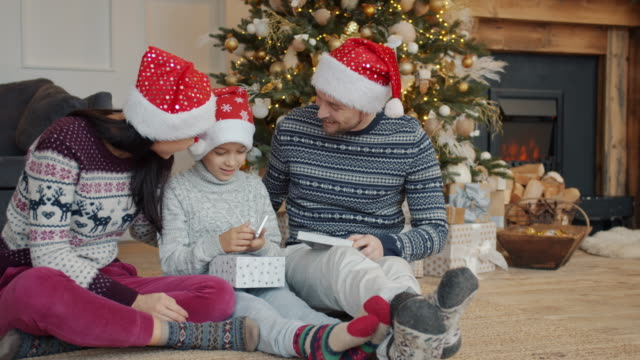 Happy kid getting modern smartphone as Christmas gift from mother and father video