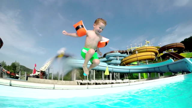 SLOW MOTION: Happy kid smiling and jumping into pool water video