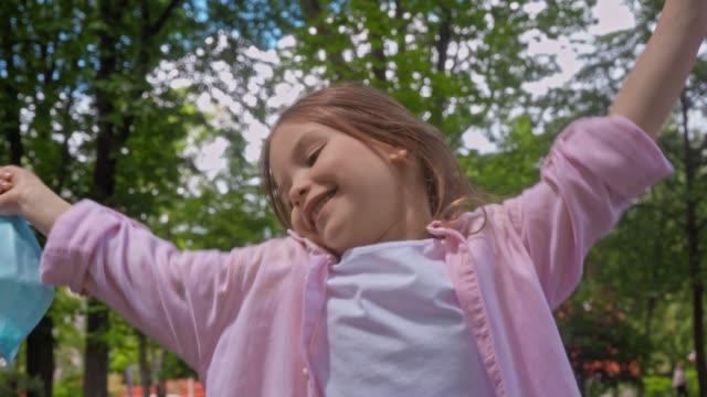 glad unge tar av medicinsk mask och sträcker sig i parken - endast flickor bildbanksvideor och videomaterial från bakom kulisserna