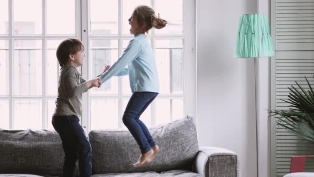 glada barn pojke och flicka som har kul hoppa på soffan - förskoleelev bildbanksvideor och videomaterial från bakom kulisserna