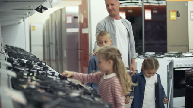 vídeos de stock e filmes b-roll de happy kids enjoying shopping in home appliance store with dad - cooker happy