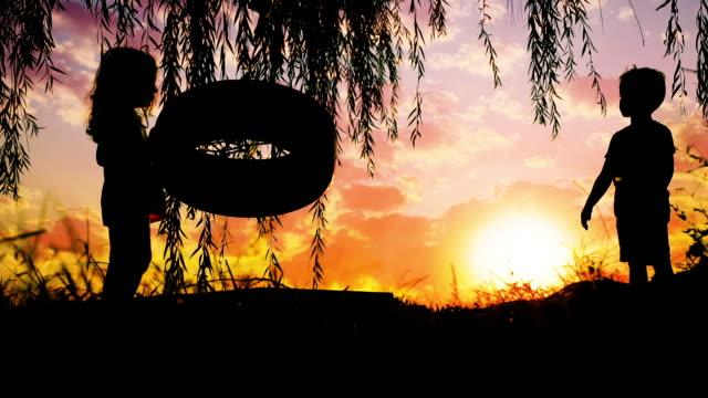 glückliche kinder, die bei schönem sonnenuntergang spaß am outdoor-spiel mit schaukel am see haben - kind schaukel stock-videos und b-roll-filmmaterial