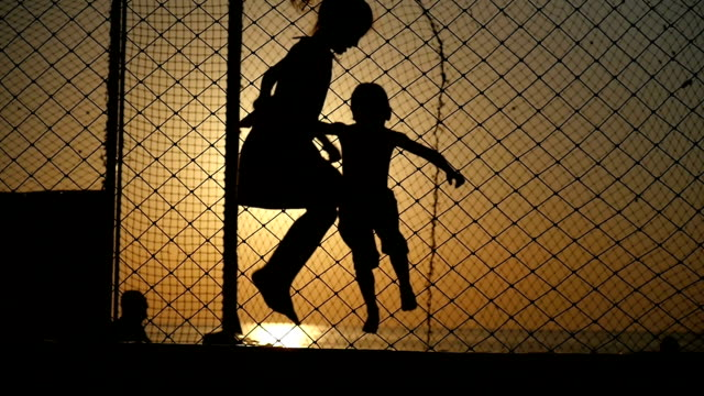 happy kids jumping on the trampoline on a background of ocean sunset silhouettes of boy and girl jumping on the trampoline on a background of ocean sunset backlit in slow motion action movie stock videos & royalty-free footage