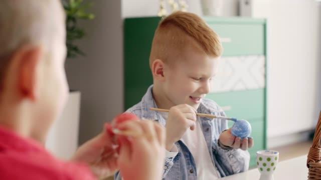 Happy kids painting easter eggs
