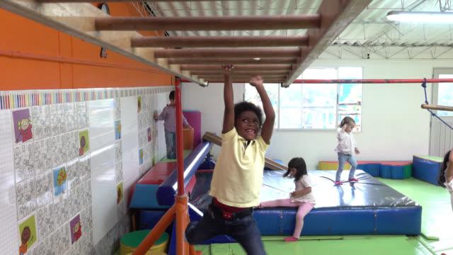 vídeos y material grabado en eventos de stock de niños felices jugando en el parque interior en la escuela que se divierten - gimnasia