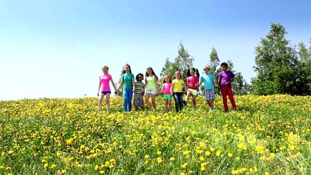 Happy kids run together in dandelion field video