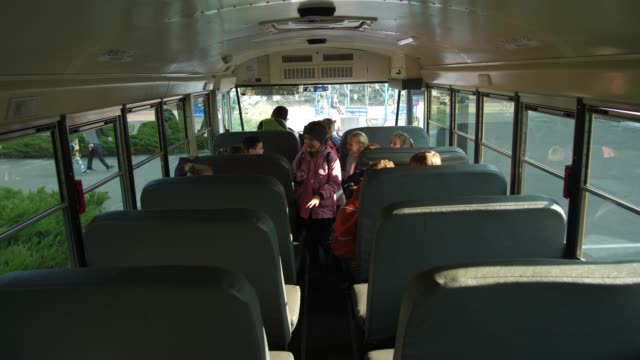 vídeos y material grabado en eventos de stock de niños felices tomando lugares en el autobús escolar para ir a casa - autobuses escolares