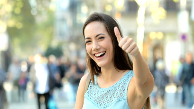happy lady gesturing thumb up in the street - thumbs up стоковые видео и кадры b-roll