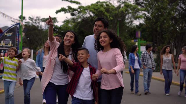 glückliche latein-amerikanischen familie in einem freizeitpark zeigt weg sprechen sehr aufgeregt - volksfest stock-videos und b-roll-filmmaterial