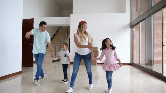 happy latin american family with two kids walking into their new home and children excited looking at everything - new home stock videos & royalty-free footage