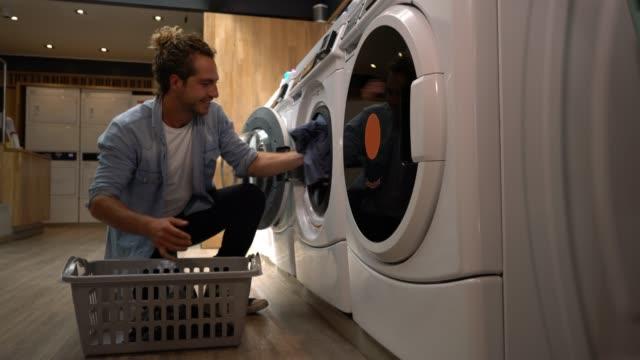 Client de mâle heureux d'Amérique latine à une laverie automatique, chargement de la machine à laver - Vidéo