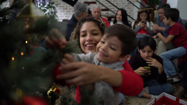 vídeos y material grabado en eventos de stock de feliz latinoamericano madre e hijo colgando adornos en un árbol de navidad sonriendo - christmas family